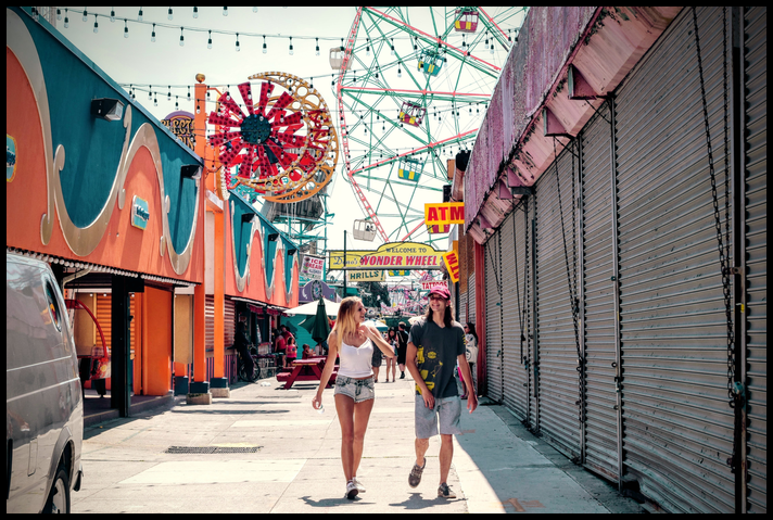 Young couple walking through a closed, colorful, carnival. class=