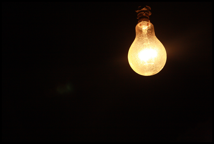 Single bright, old-fashioned lightbulb against black background. class=